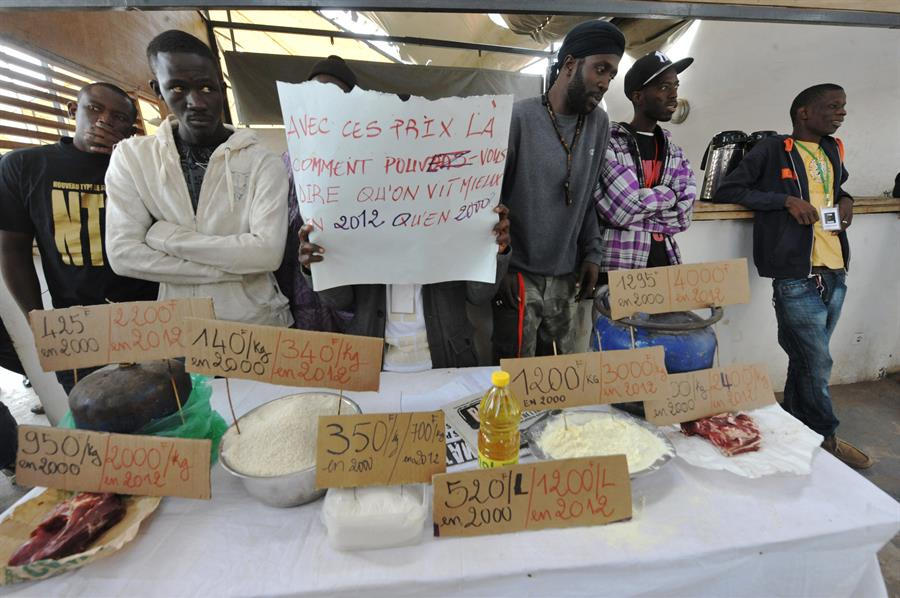 Getty Images Young Men Stand In Front Of A Table Displaying Basic Food Items With Signs Showing The Products' Price Increase From 2000 To 2012, At The The 'Y En A Marre' ('We're Fed Up') Citizen